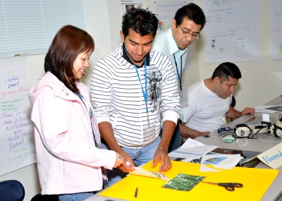 team of four students, one female and three males, creating a poster at their desks